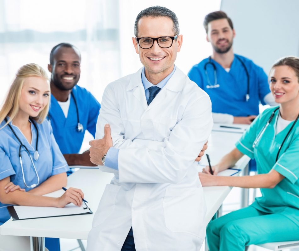 handsome general practitioner with crossed arms with colleagues sitting at table on background